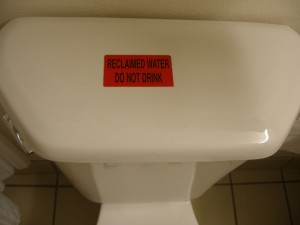 """Picture of hotel toilet cistern with notice """"Reclaimed Water - Do Not Drink."""" There are blessings of obedience."""